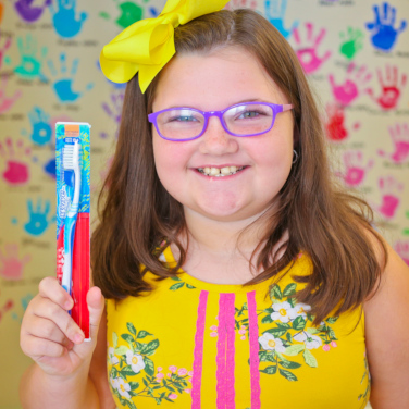 Smiling young girl with purple glasses holding up a new toothbrush.